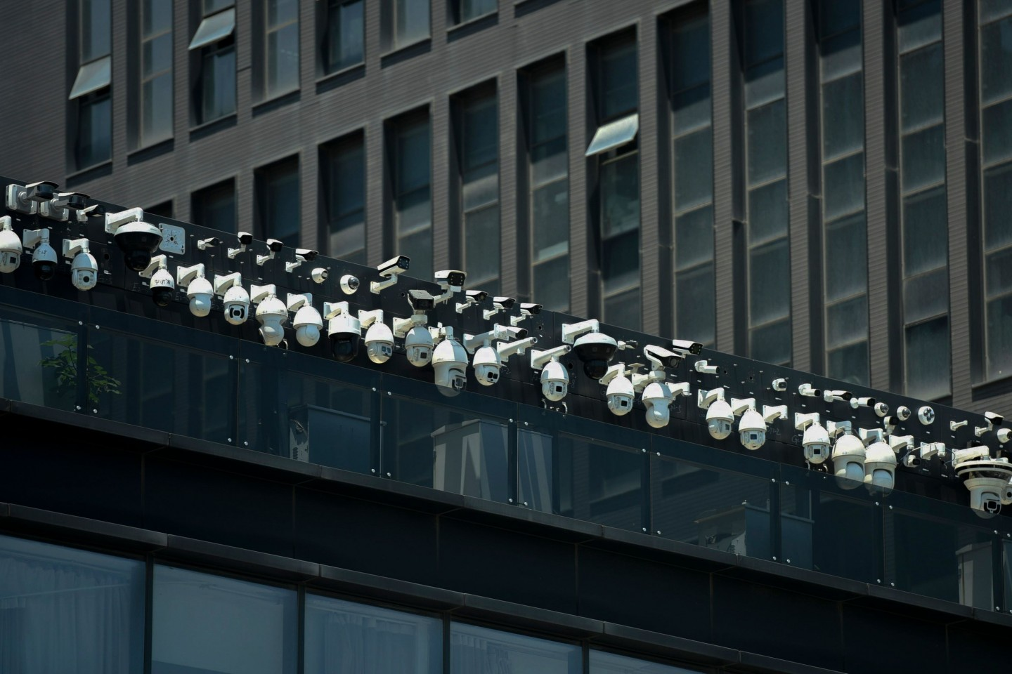 This file photo taken on 29 May 2019 shows Dahua surveillance cameras being installed on the Dahua Technologies office building in Hangzhou, in eastern China's Zhejiang province. Dahua Technology is a leading video surveillance equipment provider with an increasingly overseas footprint, with projects in Brazil, Italy, and other countries. (STR/AFP)