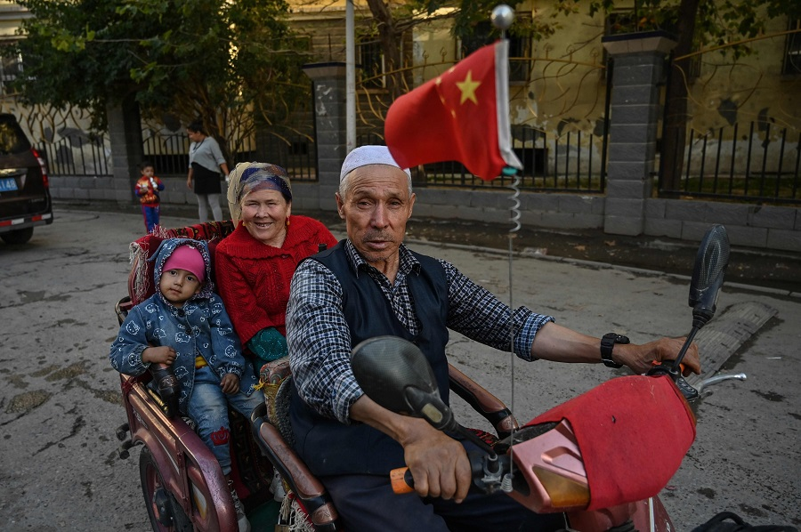 This file photo taken on 11 September 2019 shows a man driving a vehicle in an ethnic Uighur neighbourhood in Aksu in the region of Xinjiang. (Hector Retamal/AFP)