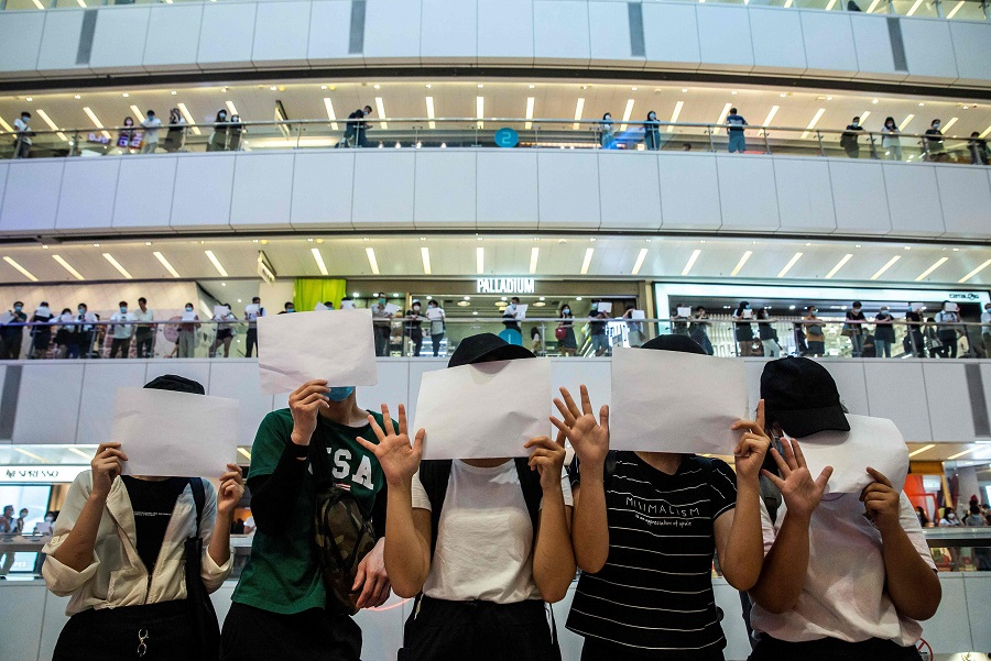 In this file picture taken on 6 July 2020, protesters hold up blank papers during a demonstration in a mall in Hong Kong, in response to a new national security law introduced in the city which makes political views, slogans and signs advocating Hong Kong's independence or liberation illegal. (Isaac Lawrence/AFP)