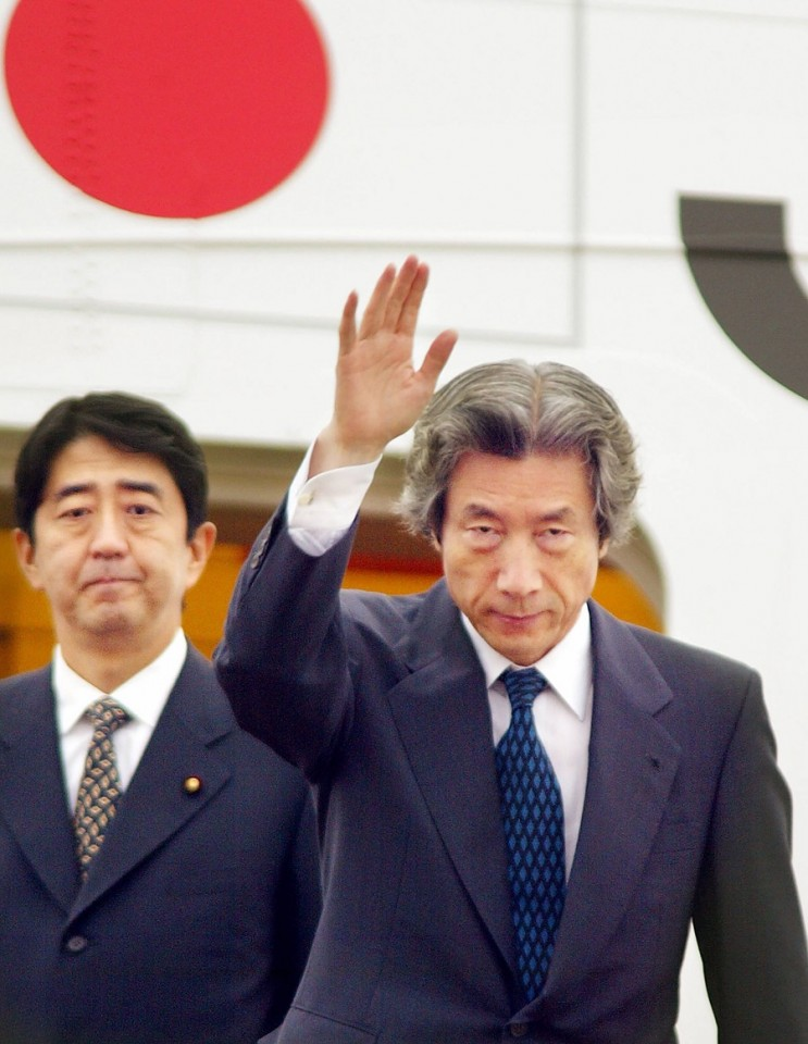 This file photo taken on 17 September 2002 shows Japanese Prime Minister Junichiro Koizumi, accompanied by then-Vice Cabinet Secretary Shinzo Abe (left), waving to well-wishers as he leaves Tokyo International Airport for Pyongyang to meet with then-North Korean leader Kim Jong Il. (Yoshikazu Tsuno/AFP)
