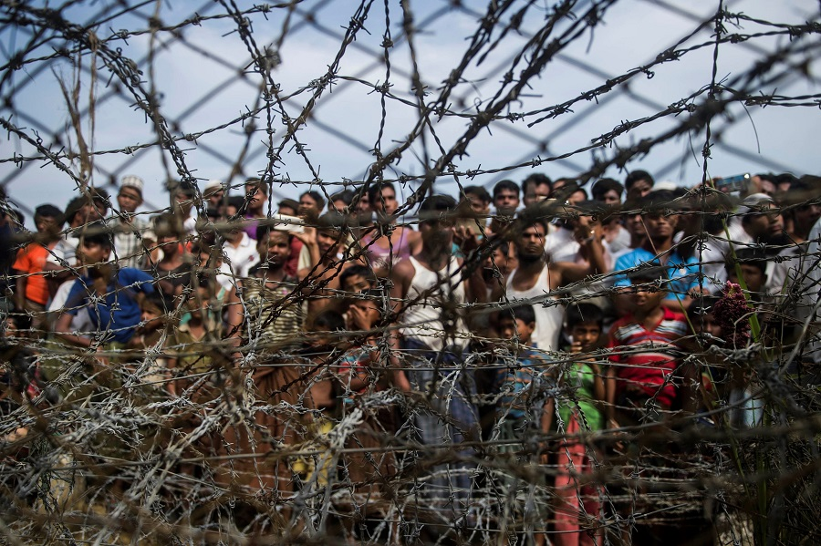"This file photo taken on 25 April 2018 shows Rohingya refugees gathered behind a barbed-wire fence at a temporary settlement setup in a ""no man's land"" border zone between Myanmar and Bangladesh, near Maungdaw district in Myanmar's Rakhine state. (Ye Aung Thu/AFP)"