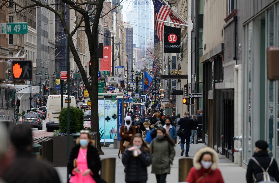 In this file photo taken on 2 April 2021, people walk on a busy 5th Avenue in midtown Manhattan, New York City, US. (Angela Weiss/AFP)
