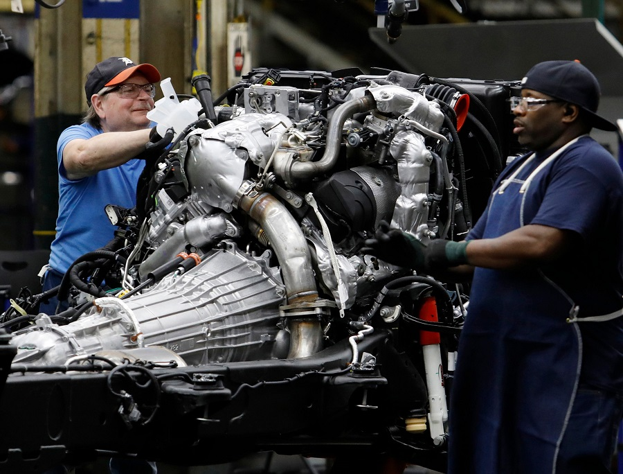 In this file photo taken on 12 June 2019, workers build the chassis of General Motors pickup trucks at the Flint Assembly plant in Flint, Michigan. (Jeff Kowalsky/AFP)