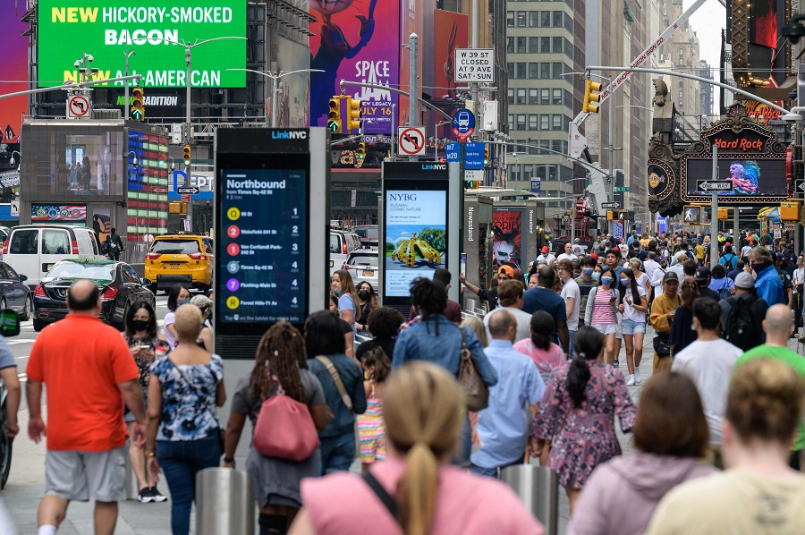In this file photo taken on 13 July 2021, people walk through Times Square in New York City, US. (Angela Weiss/AFP)