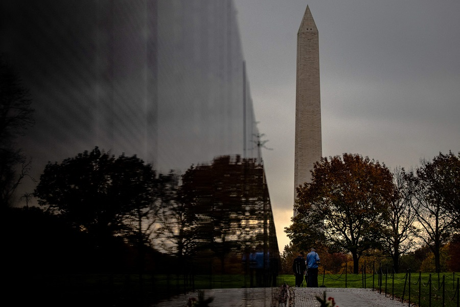 In this file photo taken on 10 November 2020, two Vietnam veterans walk towards the Washington Monument from the Vietnam Veterans Memorial Wall on Veterans Day in Washington, DC. (Samuel Corum/Getty Images North America/AFP)