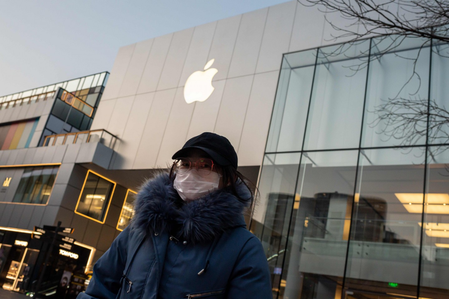 In this file photo taken on 3 February 2020, a woman wearing a protective facemask walks outside of a closed-off Apple Store in Beijing. Apple is expected to to delay the launch of its newest iPhone model originally planned for March this year. (Nicolas Asfouri/AFP)