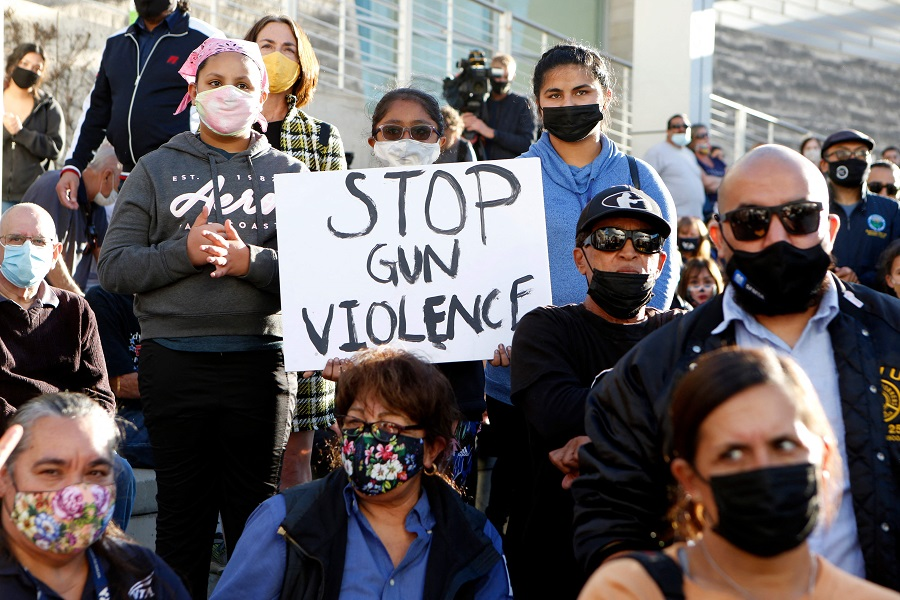 In this file photo, a girl holds a sign as people attend a vigil for the victims of a shooting at San Jose City Hall in San Jose, California, on 27 May 2021. (Amy Osborne/AFP)
