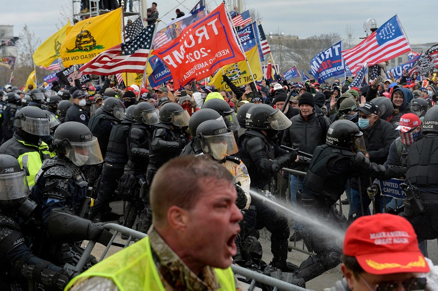In this file photo taken on 6 January 2021, Trump supporters clash with police and security forces as people try to storm the US Capitol in Washington DC. (Joseph Prezioso/AFP)