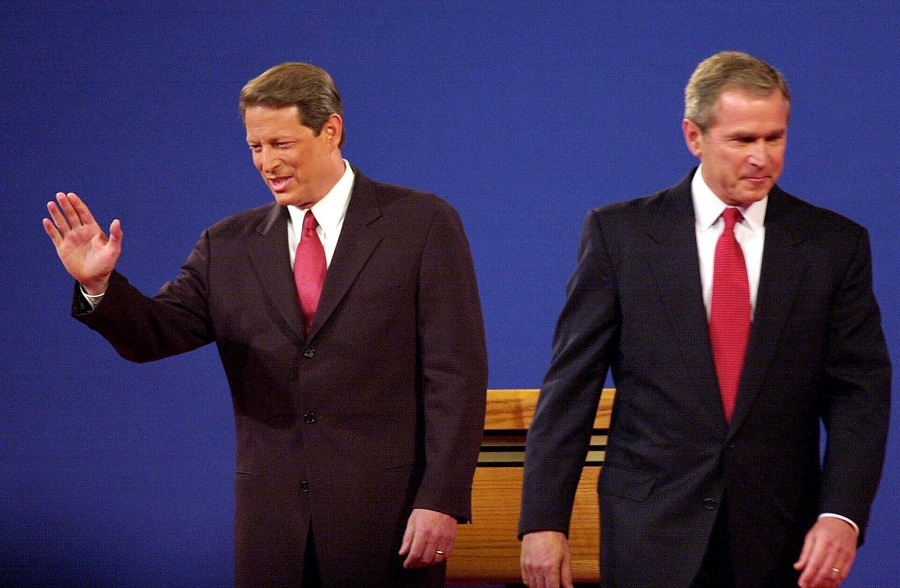 In this file photo taken on 2 October 2000, Republican presidential candidate George W. Bush and Democratic presidential candidate Al Gore move to their spots to begin their 3 October 2000 debate at the University of Massachusetts Boston. (John Mottern/AFP)