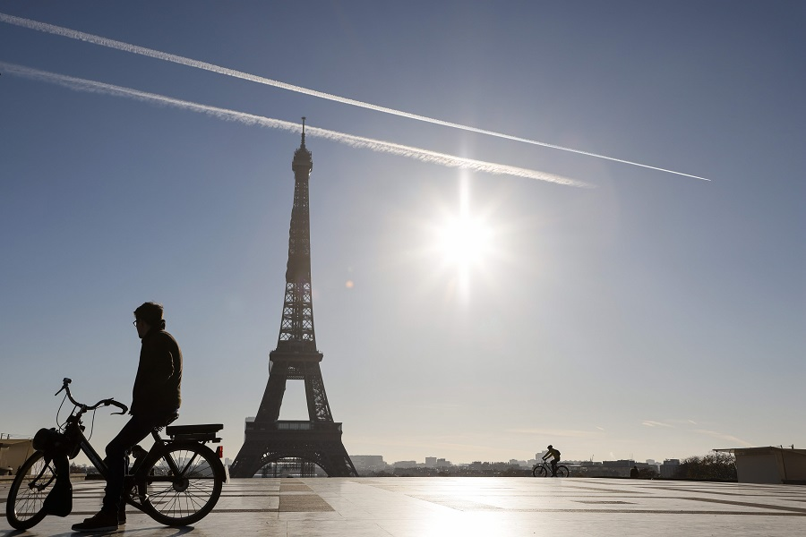 A man rides an electric bike in front of the Eiffel Tower, on the Trocadero plaza in Paris, France, on 18 November 2020. (Ludovic Marin/AFP)