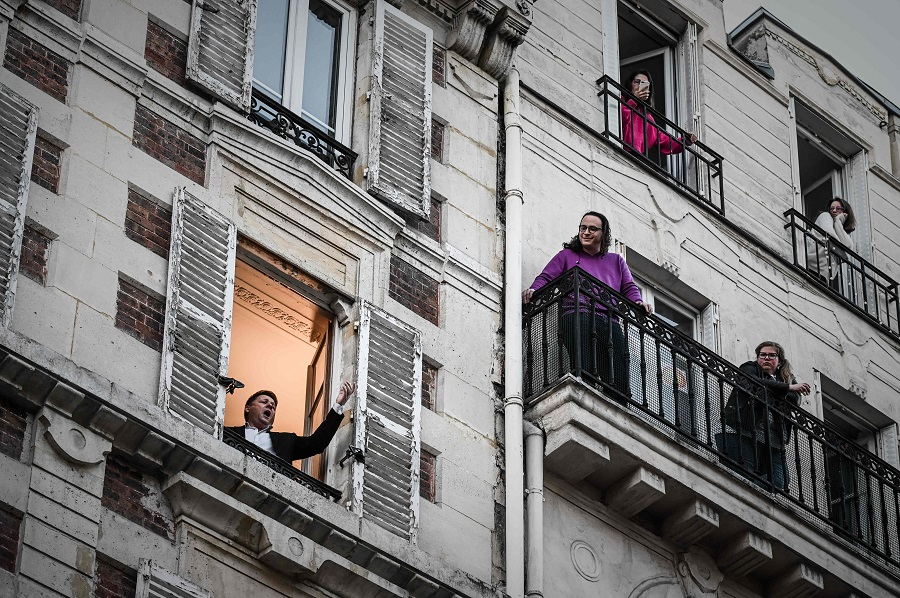 An opera tenor singer performs a song from his window in Paris on 26 March 2020. (Philippe Lopez/AFP)