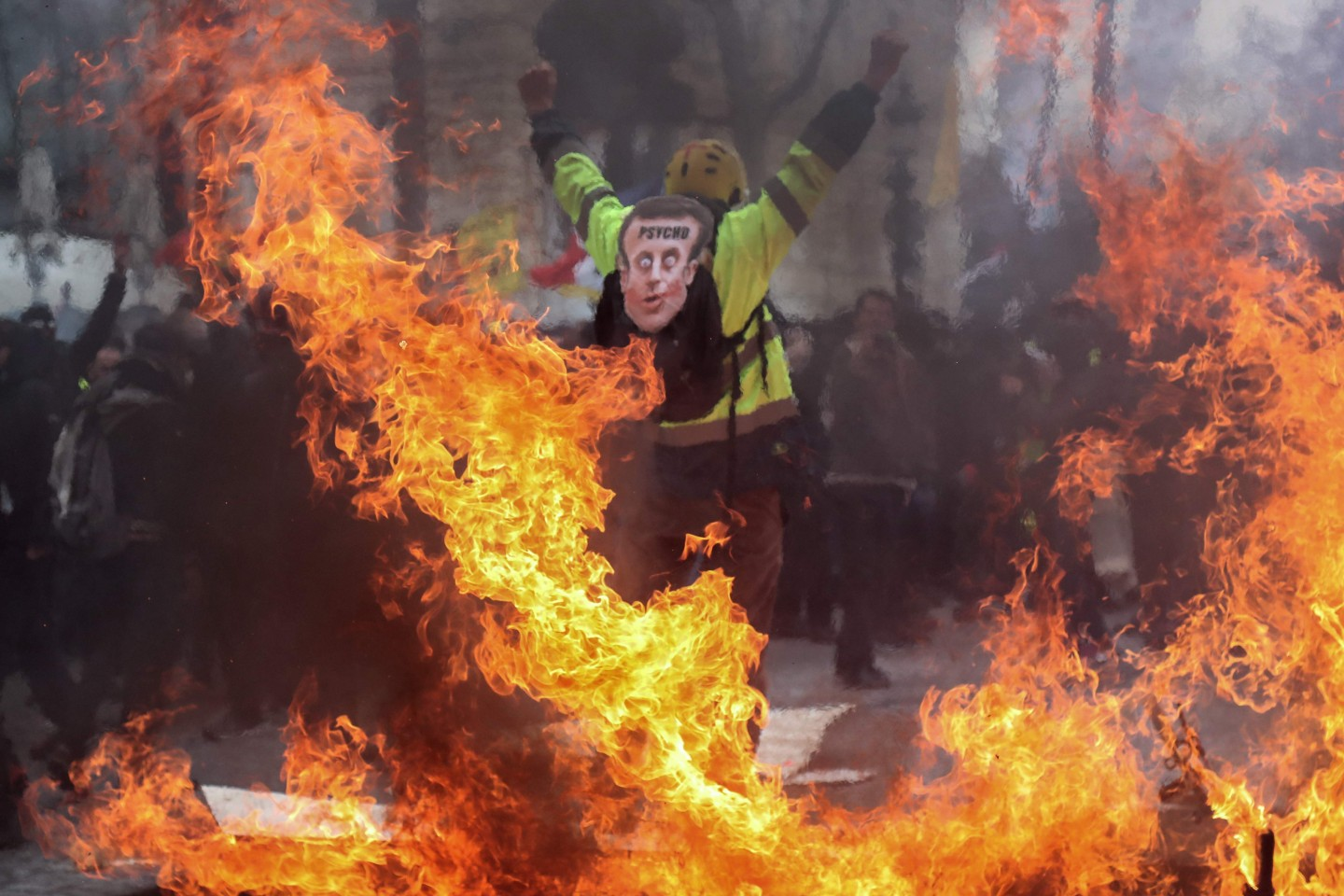 """A Yellow Vest protester wearing a mask depicting the French President on which is written 'psycho', gestures behind flames rising from barricades, in Paris on March 16, 2019, during the 18th consecutive Saturday of demonstrations called by the 'Yellow Vest' (gilets jaunes) movement. - Demonstrators hit French city streets again on March 16, for a 18th consecutive week of nationwide protest against the French President's policies and his top-down style of governing, high cost of living, government tax reforms and for more """"social and economic justice."""" (Photo by Zakaria ABDELKAFI / AFP)"""