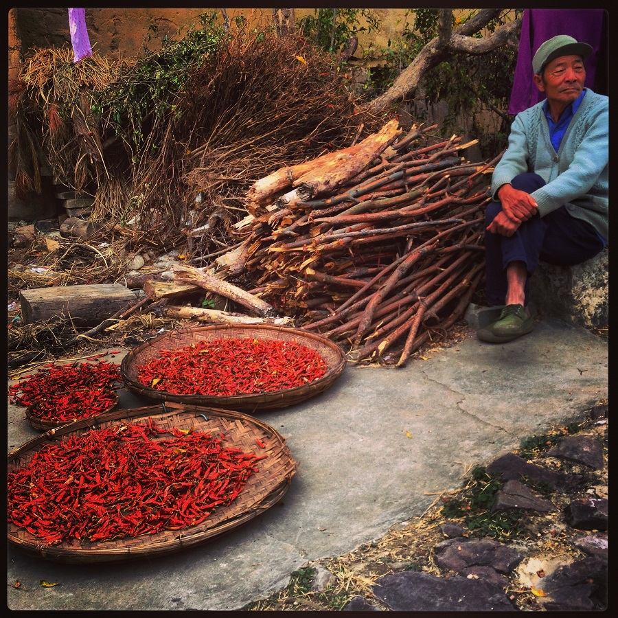 Displaying his dried red chilies in woven bamboo baskets along a village lane, this farmer in Yuanyang, Yunnan awaits buyers.