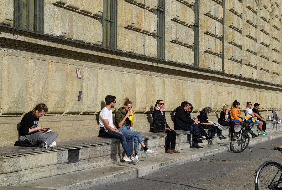 People enjoy the sunny warm weather in front of the residence at the Max-Joseph-Platz in the city of Munich, Germany, on 27 March 2020. (Christof Stache/AFP)