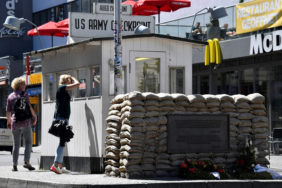 People visit Checkpoint Charlie landmark, a border crossing point between East and West Berlin during the Cold War, on 22 June 2020 in Berlin. (John Macdougall/AFP)