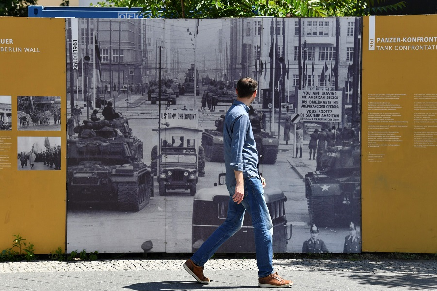 A man walks past a board displayed at Checkpoint Charlie landmark, a border crossing point between East and West Berlin during the Cold War, on 22 June 2020 in Berlin. (John Macdougall/AFP)