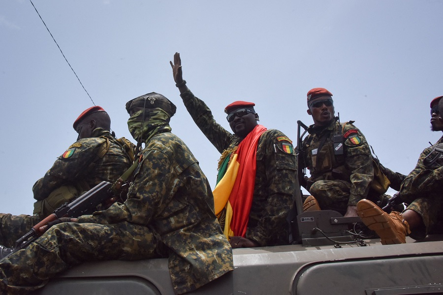 Lieutenant Colonel Mamady Doumbouya (centre), head of the army's special forces and coup leader, waves to the crowd as he arrives at the Palace of the People in Conakry, Guinea, on 6 September 2021. (Cellou Binani/AFP)