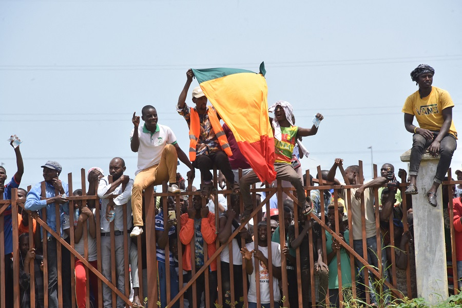 People hold up the Guinea national flag during celebrations as the Guinean Special Forces arrive at the Palace of the People in Conakry, Guinea, on 6 September 2021. (Cellou Binani/AFP)