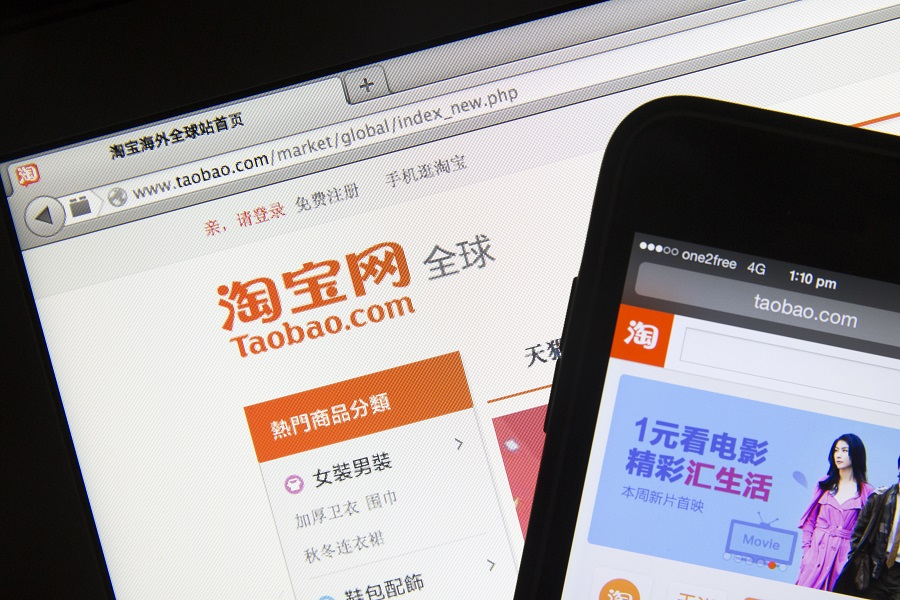 Taobao, a website of Alibaba Group Holding Ltd., is displayed on a laptop and a smartphone, in an arranged photograph taken on 21 March 2014. (Brent Lewin/Bloomberg)
