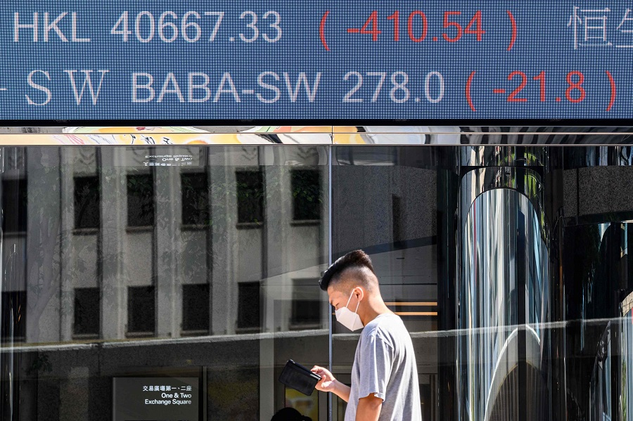 Stock activity of the Alibaba Group Holding Ltd (BABA-SW) (top) is displayed above a man as he looks at his phone while standing outside the Exchange Square towers in Hong Kong on 4 November 2020, after a last minute decision to suspend the record-breaking IPO of fintech giant Ant Group the night before. (Anthony Wallace/AFP)