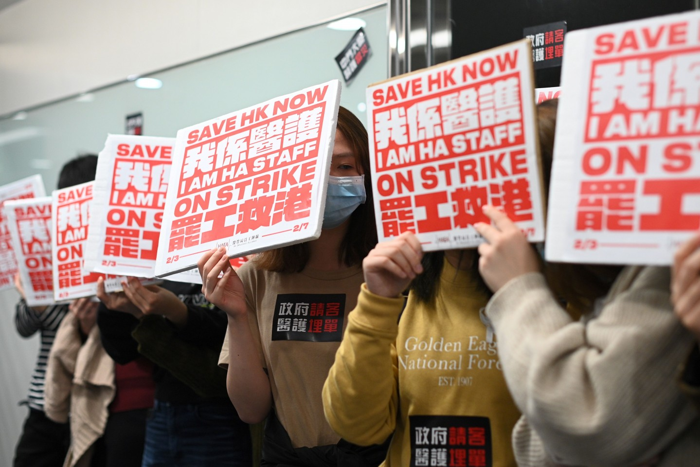 Members of the Hospital Authority Employees Alliance and other medical personnel hold placards during a strike at the Hospital Authority building in Hong Kong on 7 February 2020, calling for the government to close its border with the mainland to contain the virus outbreak. (Philip Fong/AFP)