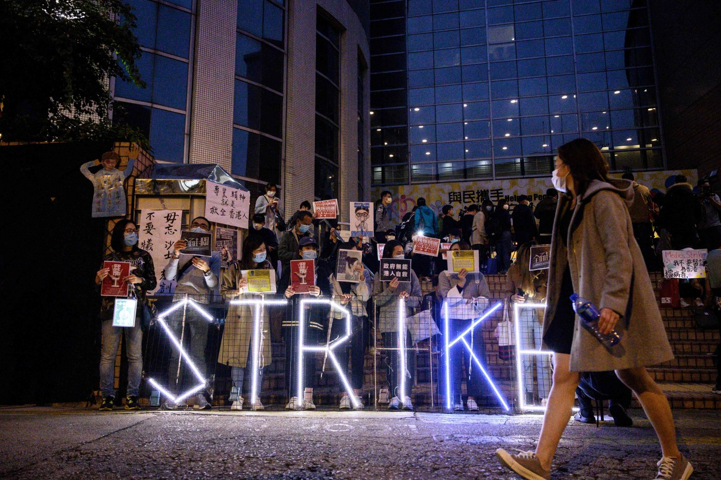 "A light installation reading ""strike"" stands before members of the Hospital Authority Employees Alliance and other activists at the Hospital Authority building in Hong Kong on 7 February 2020, calling for the government to close its border with mainland China to contain the new coronavirus epidemic. (Philip Fong/AFP)"
