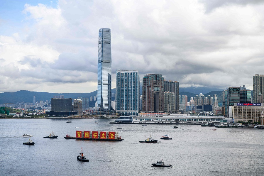 "A barge with banners that read ""Celebrate the National Security Law"" sails in Victoria Harbour. (Photo by Anthony WALLACE / AFP)"