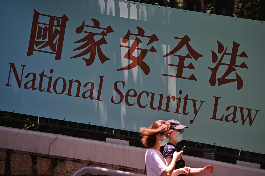 Pedestrians walk past a government public notice banner for the National Security Law in Hong Kong on 15 July  2020. (Anthony Wallace/AFP)