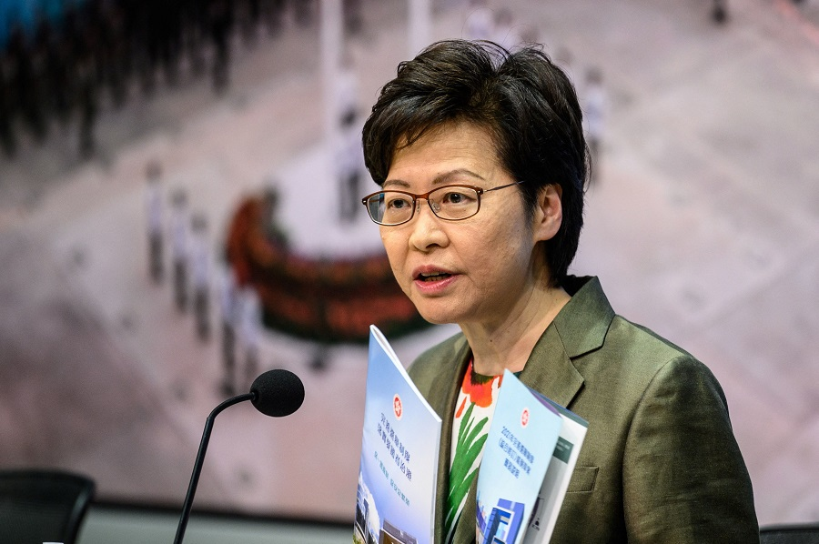 """Hong Kong Chief Executive Carrie Lam holds a pamphlet for the """"Improving Electoral System (Consolidated Amendments) Bill 2021"""" as she speaks during a press conference at the government headquarters in Hong Kong, China, on 13 April 2021. (Anthony Wallace/AFP)"""