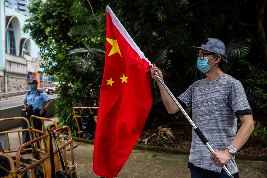 A protester (right) demonstrates outside the US consulate in Hong Kong on 8 August 2020 after the US applied sanctions on Hong Kong Chief Executive Carrie Lam and other top officials in response to Beijing enacting a national security law on the city. (Isaac Lawrence/AFP)