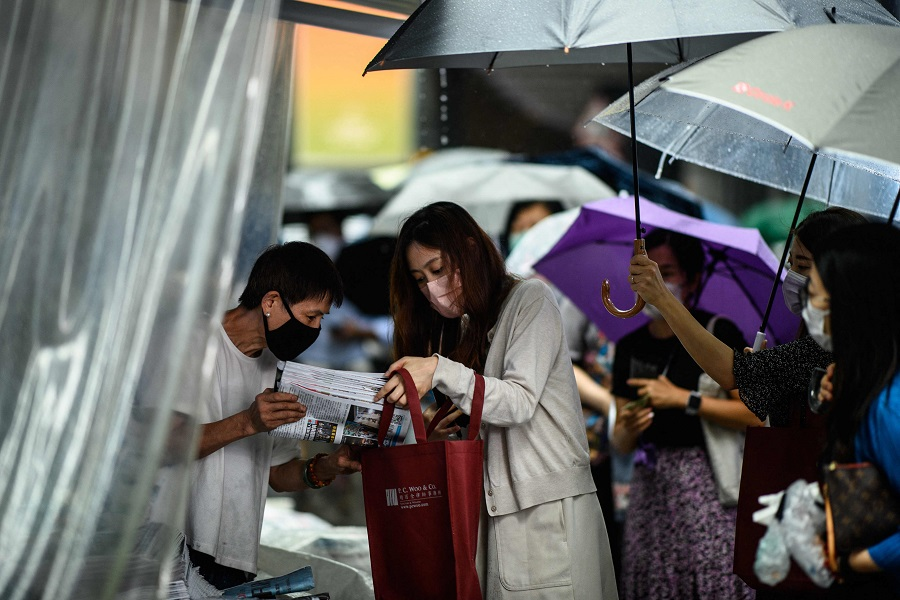 People hold umbrellas as a newsstand vendor (left) helps a customer protect her copy of the Apple Daily newspaper's final issue from the rain after she queued up to buy it from the street stall in Hong Kong, China, on 24 June 2021. (Anthony Wallace/AFP)