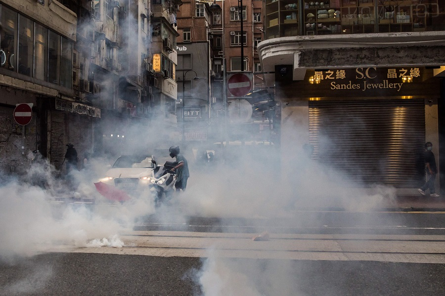 A motorist is enveloped in smoke after riot police deployed flash bangs to clear protesters from a road during a rally against a new national security law in Hong Kong on 1 July 2020. (Dale De La Rey/AFP)
