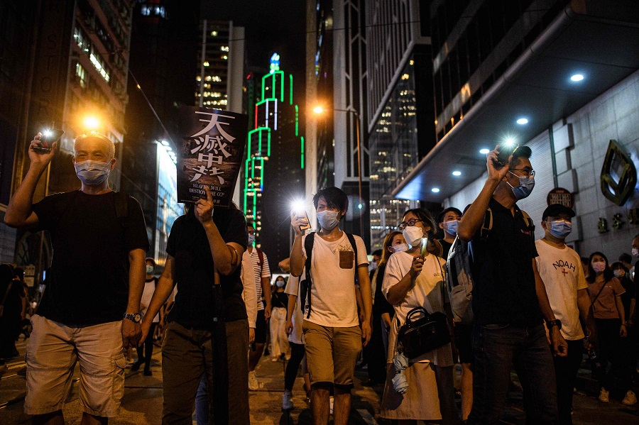 Pro-democracy protesters march in the Central district of Hong Kong on 9 June 2020, as the city marks the one-year anniversary since pro-democracy protests erupted following opposition to a bill allowing extraditions to mainland China. (Anthony Wallace/AFP)