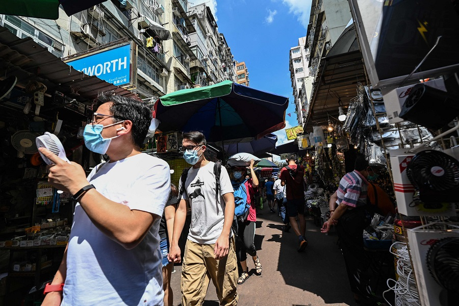 People walk through a market street in Hong Kong, China, on 22 May 2021. (Peter Parks/AFP)