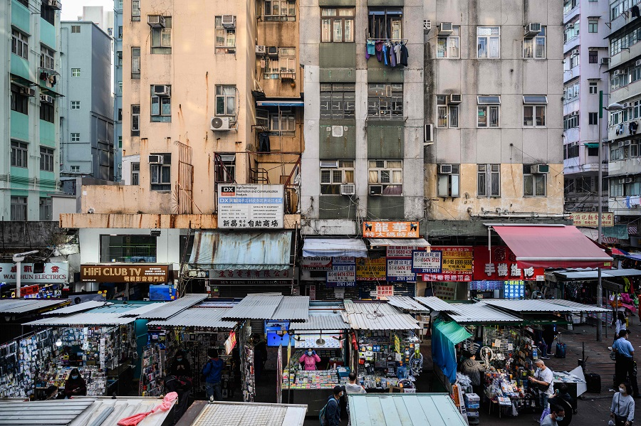 Vendors wait for customers at their street market stalls as residential buildings tower above in Hong Kong, China, on 27 January 2021. (Anthony Wallace/AFP)
