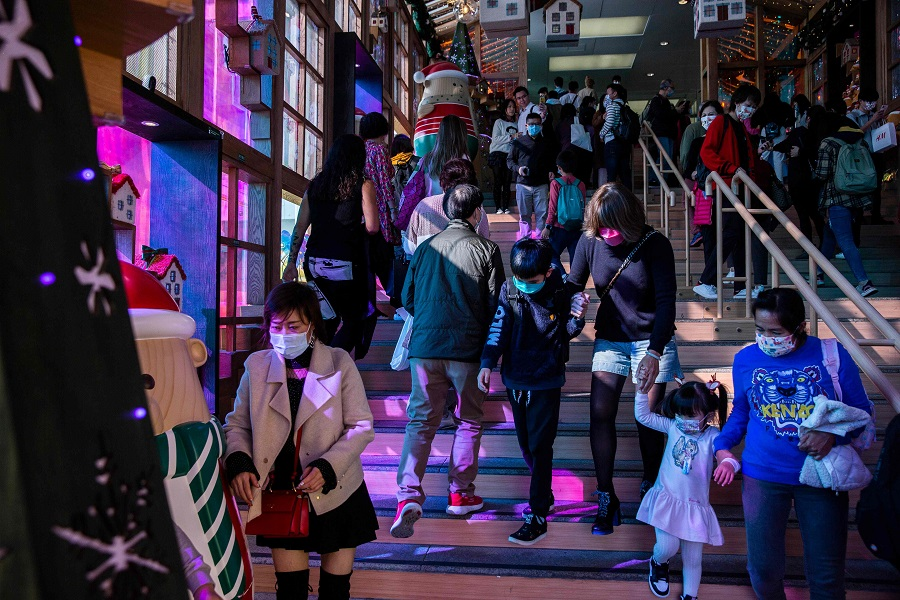 People wearing face maskswalk through a Christmas display inside a shopping mall in the Kowloon district of Hong Kong on 24 December 2020. (Isaac Lawrence/AFP)