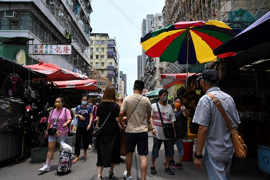 People walk around a busy shopping district in the Kowloon area of Hong Kong on 20 June 2021. (Peter Parks/AFP)