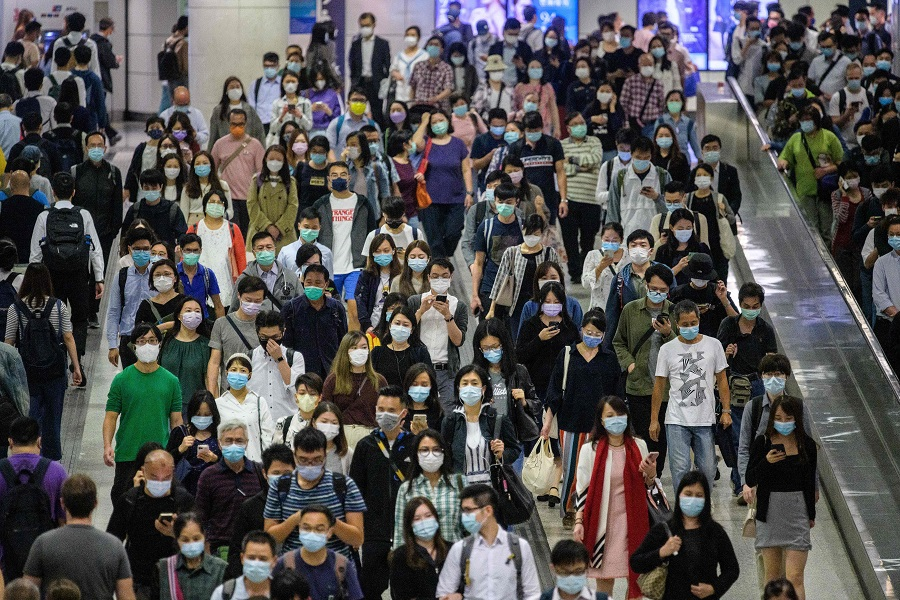 Commuters wearing face masks walk in an MTR underground metro station amid the Covid-19 coronavirus pandemic in Hong Kong on 25 November 2020. (Anthony Wallace/AFP)