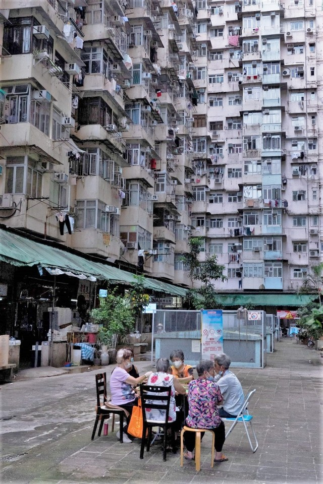 People play card games in an open area of a residential building in Hong Kong on 21 August 2021. (Bertha Wang/AFP)