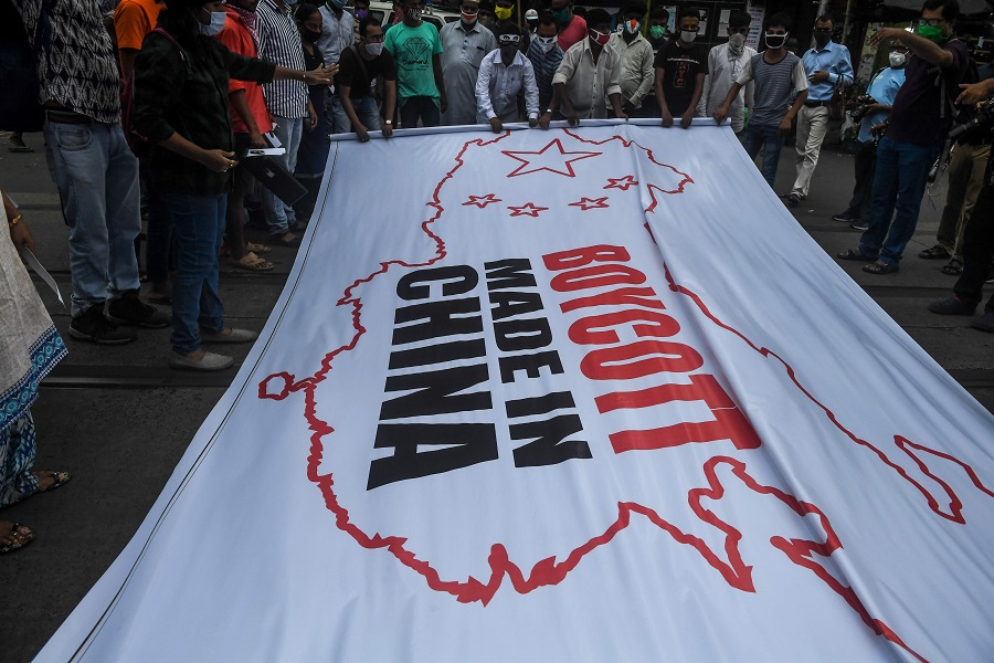 Congress party supporters hold a flag displaying the country and flag of China along with an inscription reading 'Boycott Made in China' during an anti-China demonstration in Kolkata on 18 June 2020. (Dibyangshu Sarkar/AFP)