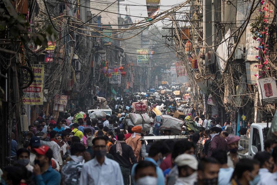 People walk along a street of a market area amid the Covid-19 coronavirus pandemic in New Delhi on 7 November 2020. (Xavier Galiana/AFP)