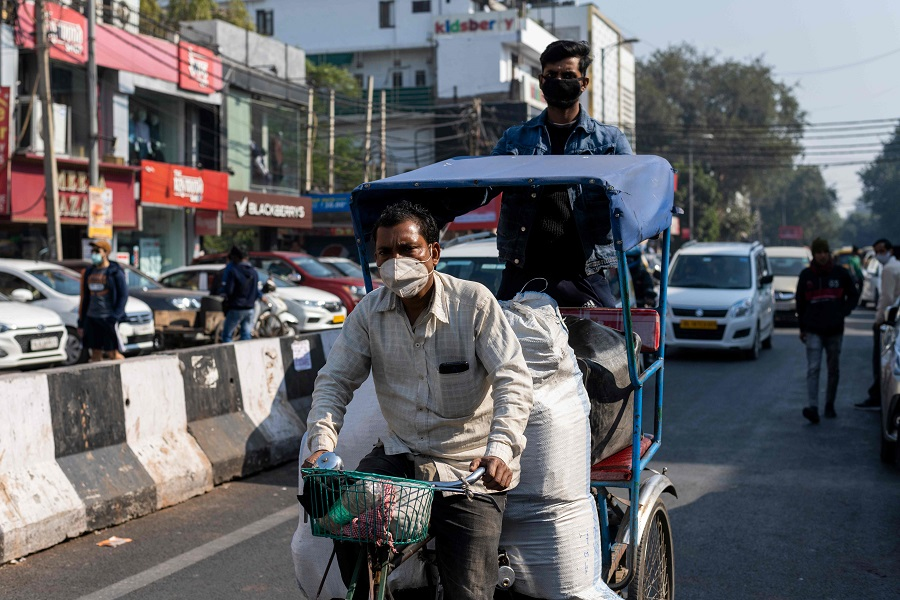 A rickshaw driver wearing a face mask transports goods along a street in a market area in New Delhi, India on 19 December 2020. (Jewel Samad/AFP)