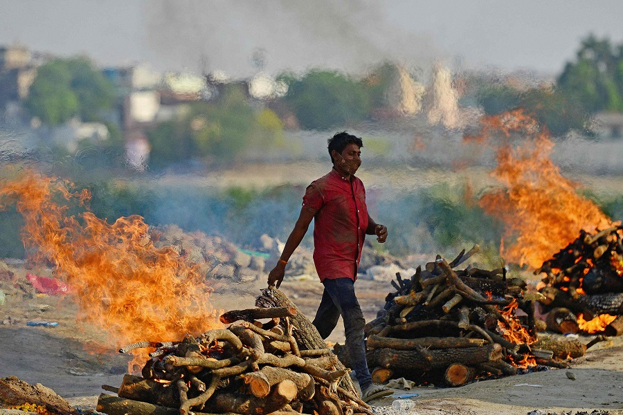 Funeral pyres burn as the last rites are performed of the patients who died of the Covid-19 coronavirus at a cremation ground in Allahabad, India, on 27 April 2021. (Sanjay Kanojia/AFP)
