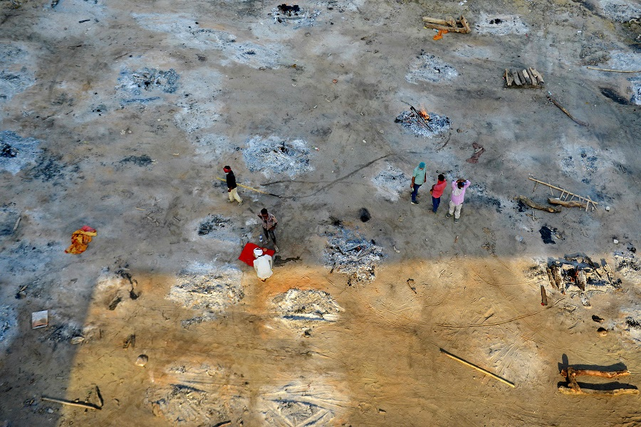 Relatives and family members can be seen as they collect the remains after performing the last rites of patients who died of the Covid-19 coronavirus at a site of a mass cremation in Allahabad, India, on 27 April 2021. (Sanjay Kanojia/AFP)