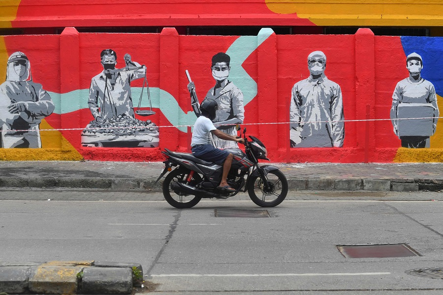 A motorist drives past a wall mural painted to thank frontline workers fighting against the Covid-19 coronavirus, in Mumbai, on 15 June 2020. (Indranil Mukherjee/AFP)