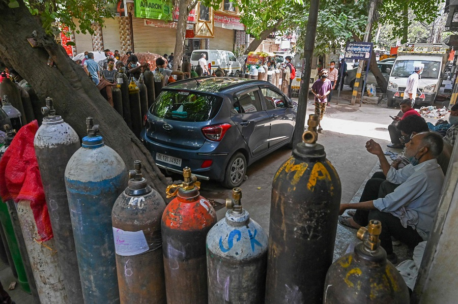People wait to refill their medical oxygen cylinders for Covid-19 coronavirus patients under home quarantine at a private refill centre in New Delhi, India, on 4 May 2021. (Prakash Singh/AFP)