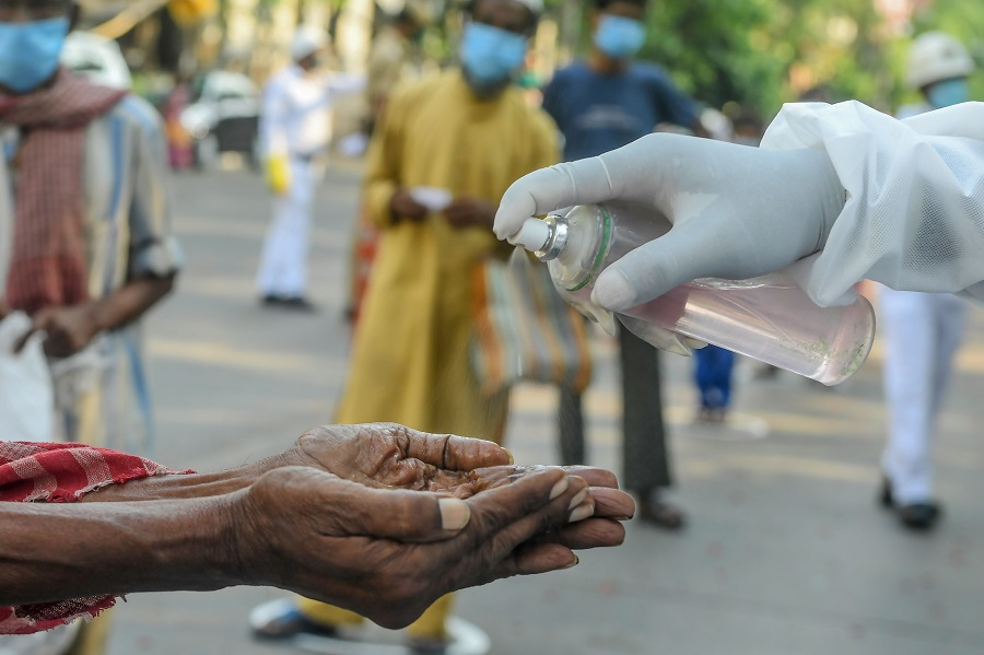 A slum dweller (left) cleans his hands with sanitiser before collecting relief material during a government-imposed nationwide lockdown as a preventive measure against the Covid-19 coronavirus, in Kolkata, India, on 30 April 2020. (Dibyangshu Sarkar/AFP)