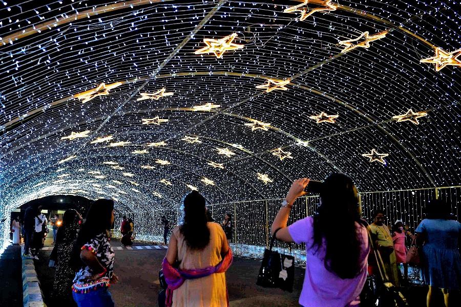 People take pictures at a shopping mall in Mumbai on 31 December 2020. (Punit Paranjpe/AFP)