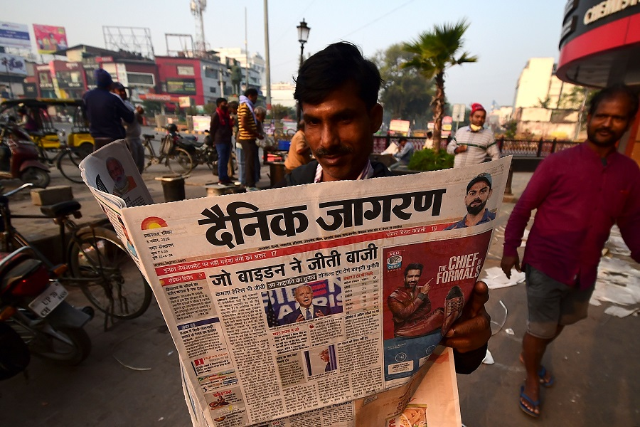 A man reads a morning newspaper showing a photograph of US President-elect Joe Biden, on a street in Allahabad, India, on 8 November 2020. (Sanjay Kanojia/AFP)