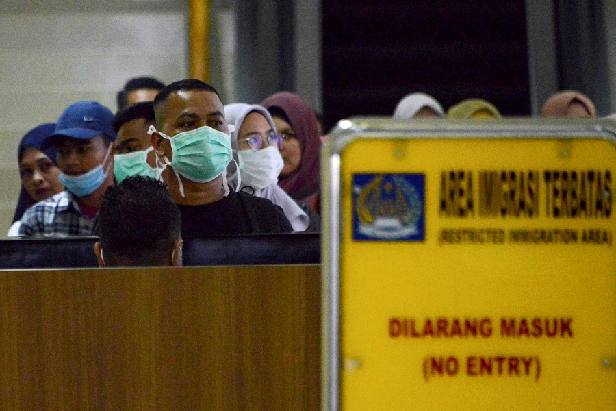 Passengers wearing facemasks to help stop the spread of a deadly virus which began in the Chinese city of Wuhan, pass through immigration upon arrival at the Sultan Iskandar Muda International Airport in Blang Bintang, Aceh Besar, on 27 January 2020. (Chaideer Mahyuddin/AFP)